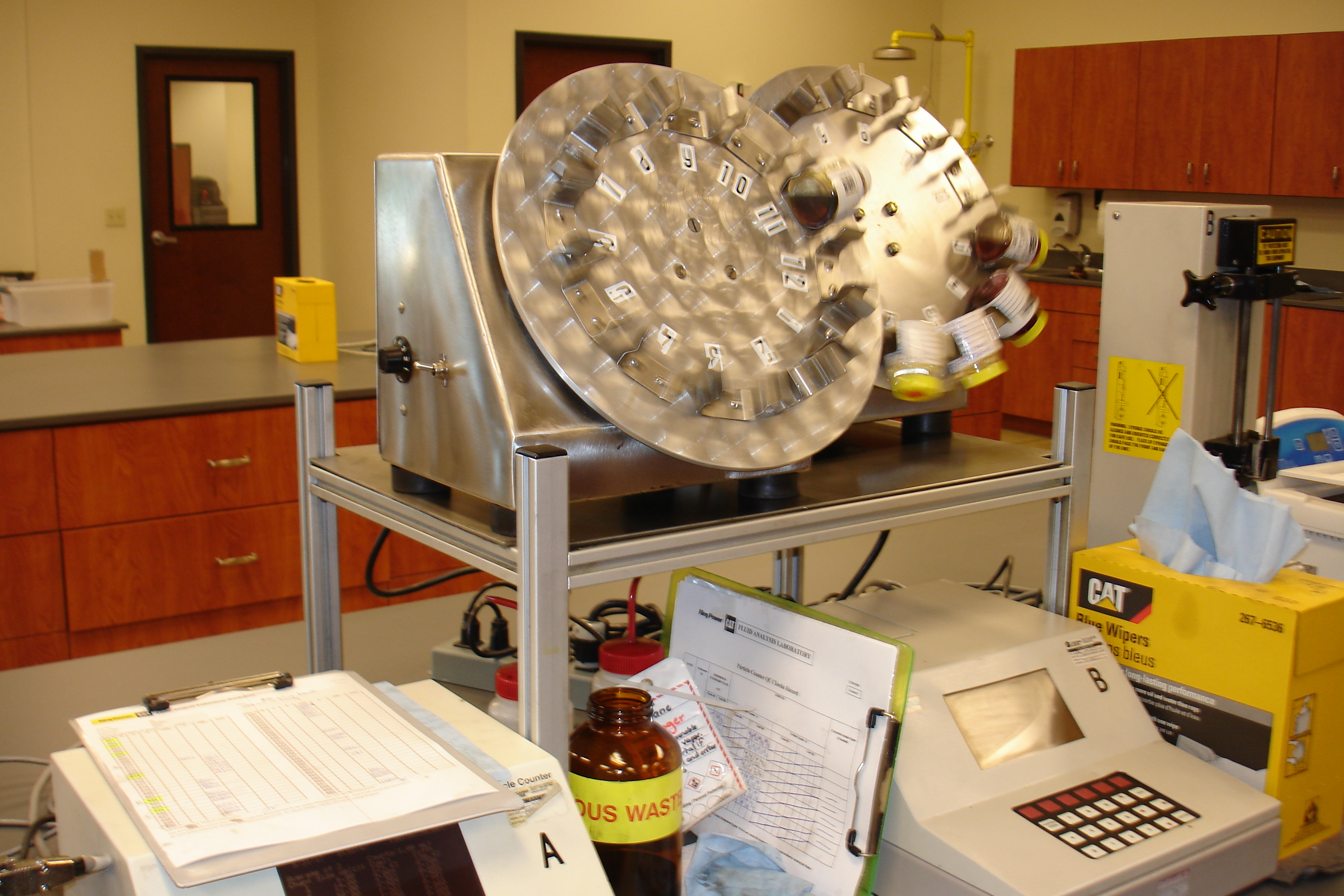 Two rotation wheels gently disperse the particles throughout the sample before particle count testing.