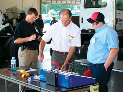 Ring Power Training Instructor Bob Delp explains the electrical fundamentals test objectives to SkillsUSA competitor.